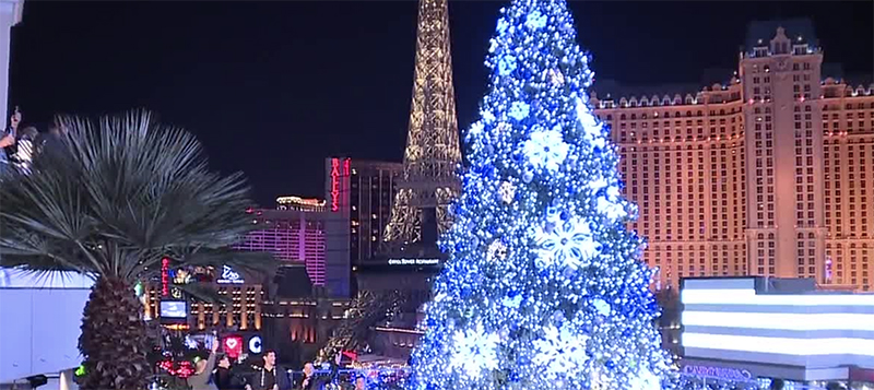 Christmas Bonuses in Las Vegas With Cosmopolitan Las Vegas Christmas Tree Lit Up And Planet Hollywood And Eiffel Tower From Paris Hotel As Background